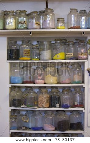 Display of colored sand inside cans