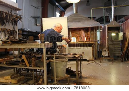 An Artisan At Work Making Glass Sculpture