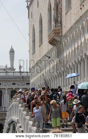 Crowd of people crossing a bridge