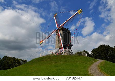 Windmill on a grassy hill in Bruges, Belgium