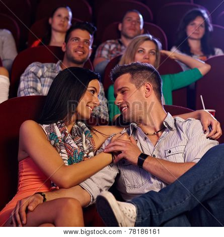 Loving young couple embracing, kissing in movie theater.