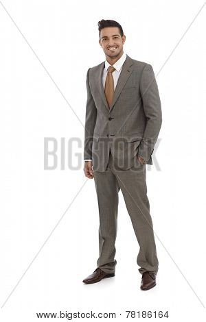 Elegant businessman smiling in grey suit over white background.