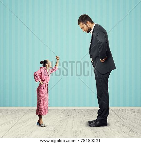 displeased man looking at small angry woman