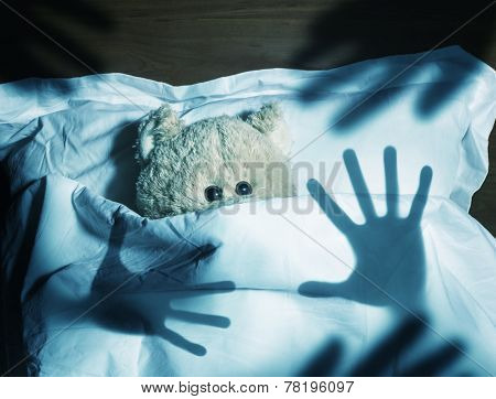 Adorable teddy bear laying in bed, scared