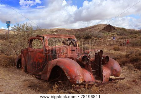 Old car rusting in Desert Landscape with Barn in Background