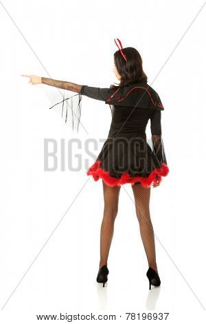 Back view of woman pointing left wearing devil clothes.