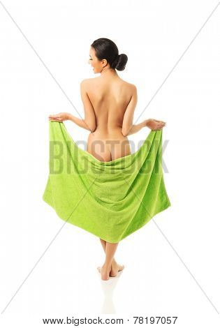 Back view of woman standing wrapped in green towel