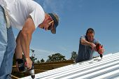 stock photo of rafters  - Construction roofing crew uses power tools to screw and fasten sheet metal to the roof rafters of a building - JPG
