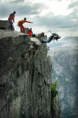 image of jump rope  - Man jumping off a cliff with a rope - JPG