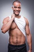 image of toothless smile  - Handsome young African man taking off his tank top and smiling while standing against grey background - JPG