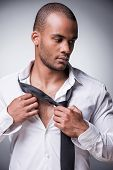 stock photo of take off clothes  - Confident young black man taking off his necktie while standing against grey background - JPG