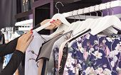 pic of boutique  - Female clothes on hangers in fashion boutique  - JPG
