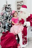 foto of saint-nicolas  - little girl in a beautiful pink dress sits on a lap at Saint Nicolas about a New Year tree - JPG