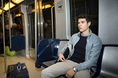 stock photo of commutator  - Young man sitting in subway train commuting to work looking away - JPG