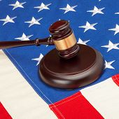 picture of supreme court  - Wooden judge gavel and soundboard laying over US flag  - JPG