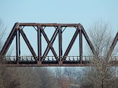 stock photo of trestle bridge  - a old iron and steel train trestle that goes over another set of railroad tracks - JPG