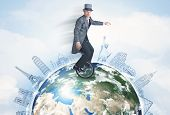 image of unicycle  - Man riding unicycle around the globe with major cities concept  - JPG