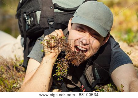Young hungry man tourist surviving by eating grass and roots in forest.