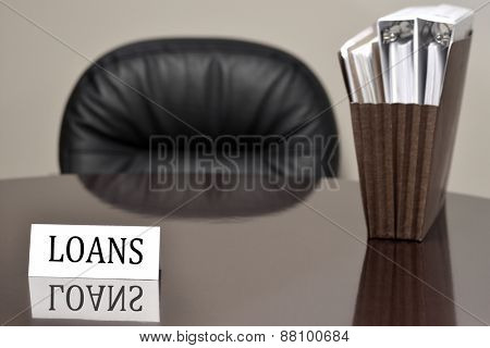 Business card for loans lending on desk with files and chair