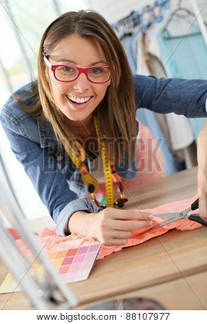 Fashion designer cutting fabric on dressmaking table
