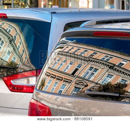 beautiful old houses are reflected in the windows of a car