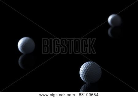 Several golf balls isolated on black background with blank copy space for text.