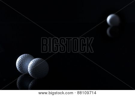 Few golf balls isolated on black background with empty copy space for text.