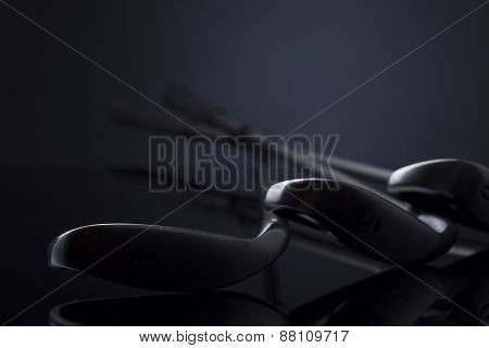 Close up of golf clubs lying on reflective surface, isolated on dark blue background, empty copy space for text.