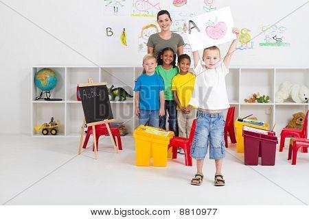preschool boy showing his artwork