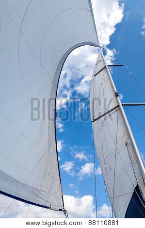 Sails filled with wind against the sky with clouds