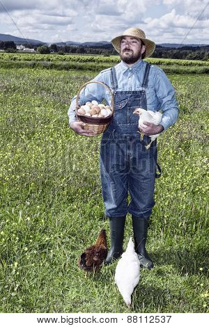 Farmer In Field With Chicken And Organic Eggs