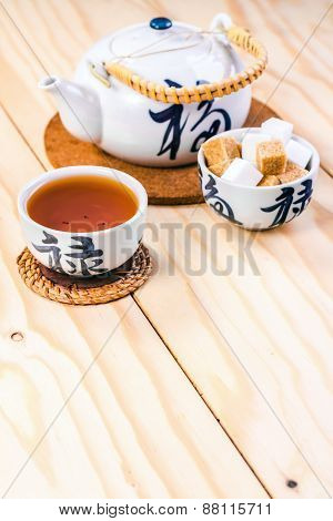Chinese cup of tea and kettle on wooden table