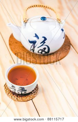 Chinese cup and kettle of tea on wooden table