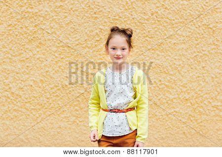 Fashion portrait of a cute little girl of 7 years old, wearing blouse, yellow jacket, orange belt