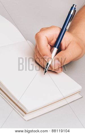 Man's hand with pen, writing something