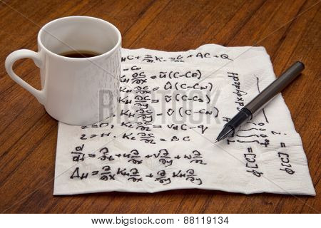mathematical equations of physics - handwriting on a napkin with a coffee cup and pen