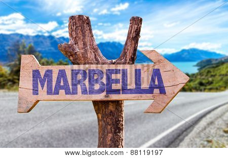 Marbella wooden sign with road background