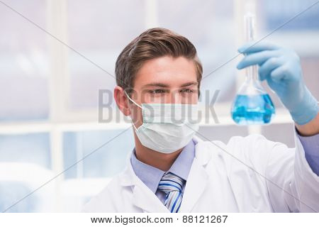 Scientist examining beaker with blue fluid in laboratory