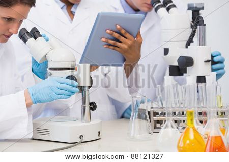 Scientists working with microscope and tablet in laboratory