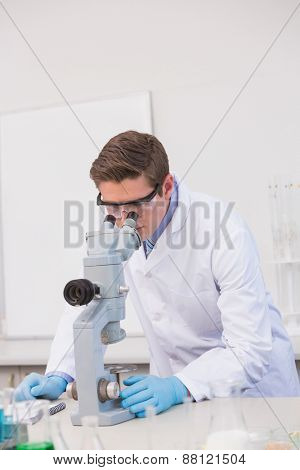 Scientist looking through a microscope in laboratory