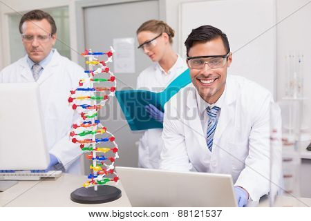 Scientist working together with laptop and computer in laboratory
