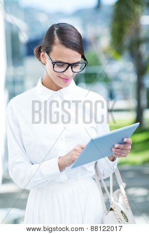 Pretty woman using her tablet pc outside