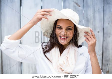 Smiling beautiful brunette wearing straw hat and looking at camera on wooden plank background