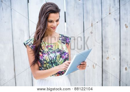Smiling beautiful brunette using her tablet on wooden plank background