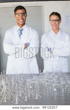 Smiling scientists looking at camera arms crossed in laboratory