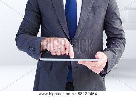Businessman using his tablet pc against abstract white design