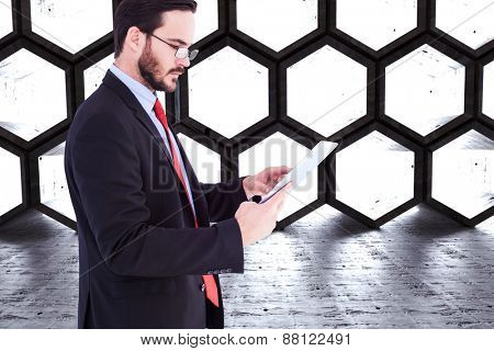 Businessman scrolling on his digital tablet against hexagon room