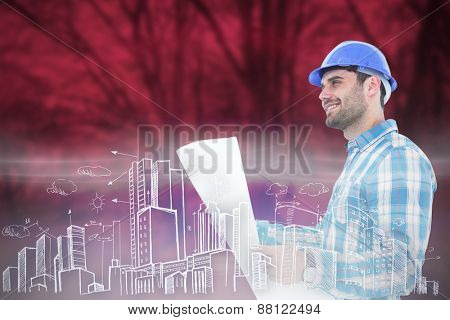 Smiling engineer looking away while holding blueprint against purple forest