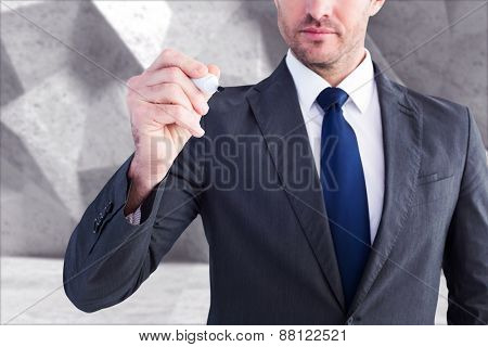 Serious businessman writing with marker against grey angular background