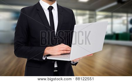 Mid section of a businessman using laptop against fitness studio